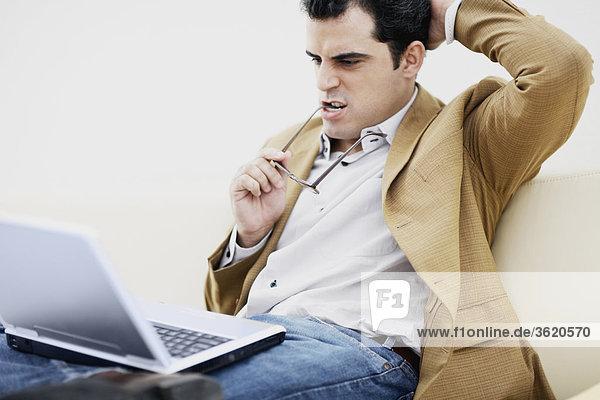 Nahaufnahme eines Mitte erwachsenen Menschen sitzen mit einem Laptop und denken