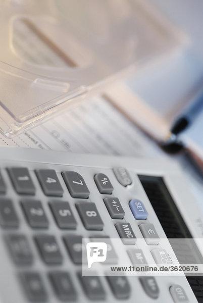 Nahaufnahme Taschenrechner mit einem Stift auf Dokumente