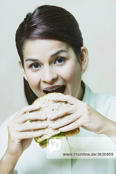 Close-up of a young woman eating a sandwich