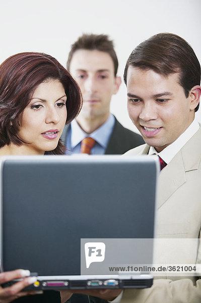 Zwei Geschäftsleute und eine geschäftsfrau  Blick auf einem laptop