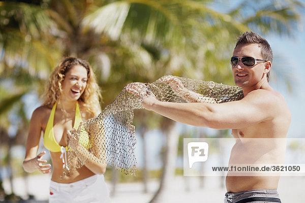 Junges paar Standing am Strand und halten ein Fischernetz