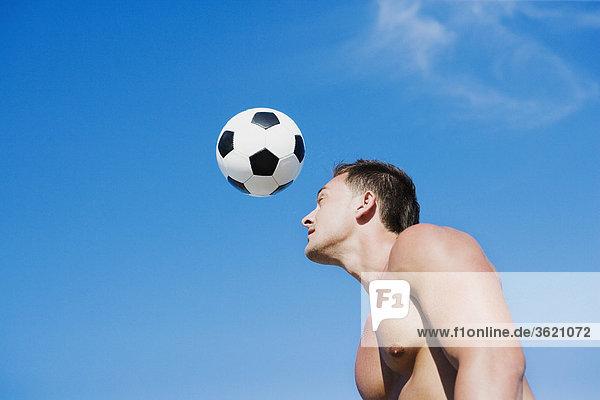 Seitenansicht eines jungen Mannes mit einem Fußball spielen