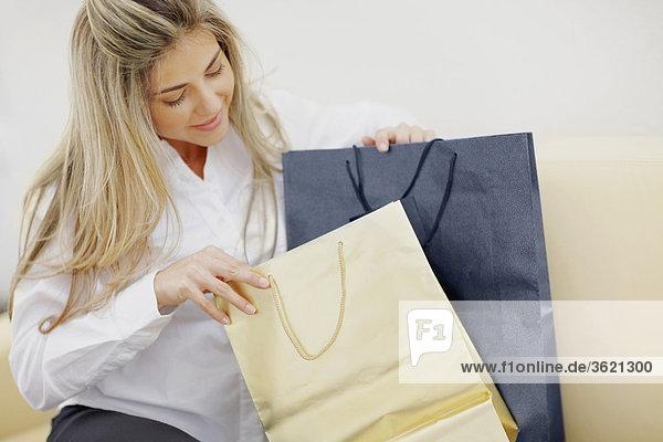 Nahaufnahme einer Mitte erwachsen Frau sitzend mit Einkaufstaschen