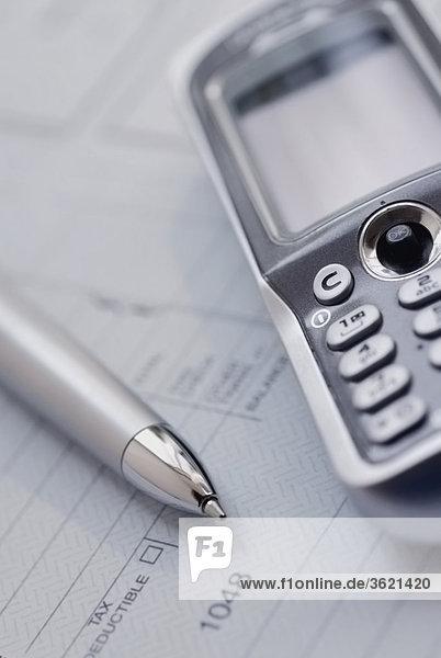 Nahaufnahme von einem Mobiltelefon und einem Stift auf ein Dokument