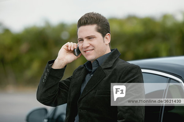 Close-up of a young man leaning against a car and talking on a mobile phone