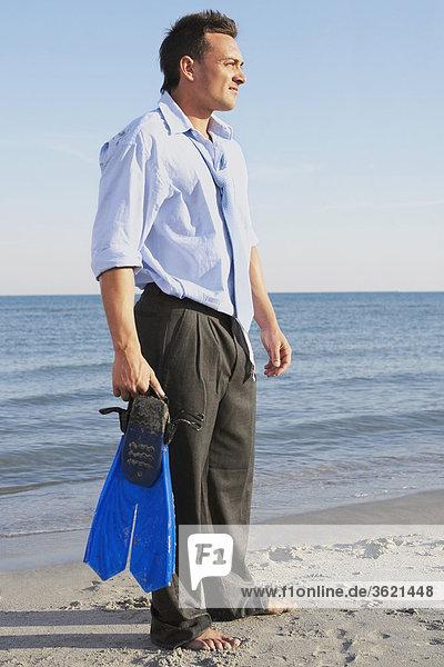 Seitenansicht eines jungen Mannes hält Flipper und stehen am Strand