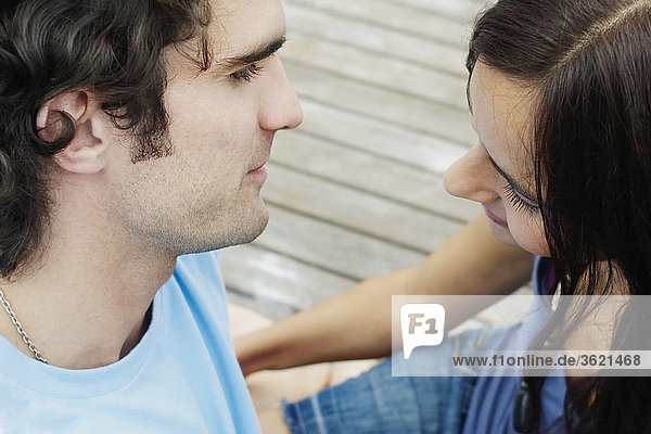 High angle view of a young couple sitting at a pier and looking at each other