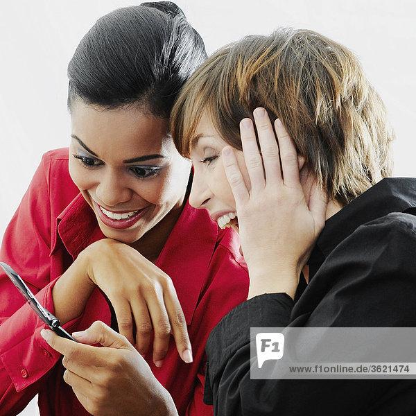 Nahaufnahme der zwei jungen Frauen betrachten ein Mobiltelefon und lächelnd