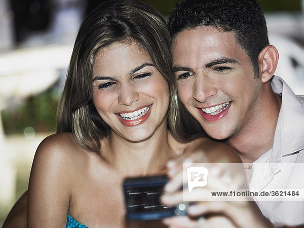 Close-up of a teenage boy taking a picture of himself with a young woman