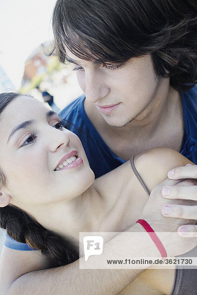 Close-up of a young man embracing a young woman from behind