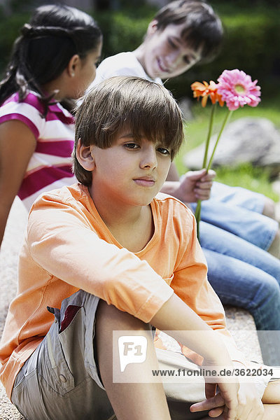 Nahaufnahme eines jungen mit seinen Freunden sitzen hinter ihm denken