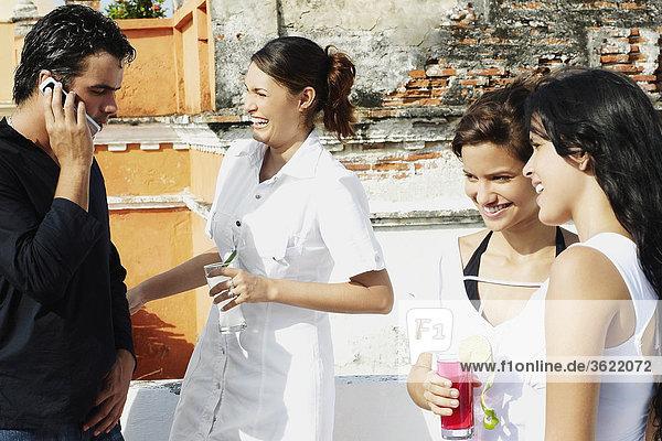 Junger Mann und drei jungen Frauen stehen auf einer Terrasse