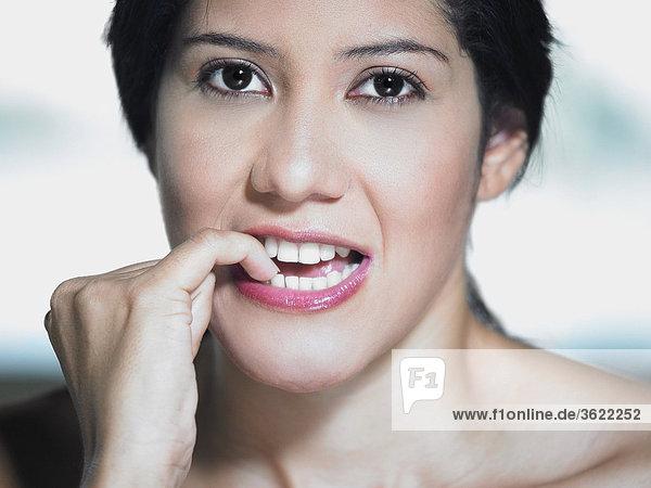 Portrait einer jungen Frau beißt ihre Nägel