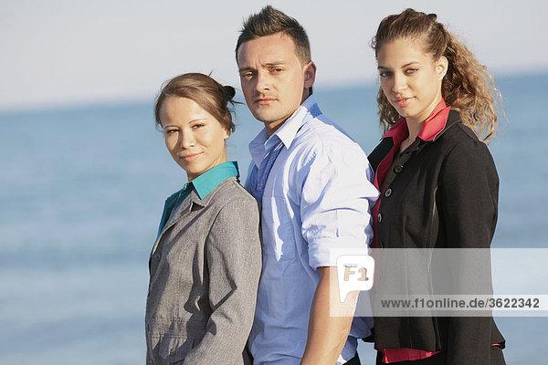 Porträt eines jungen Mannes mit zwei junge Frauen stehen am Strand