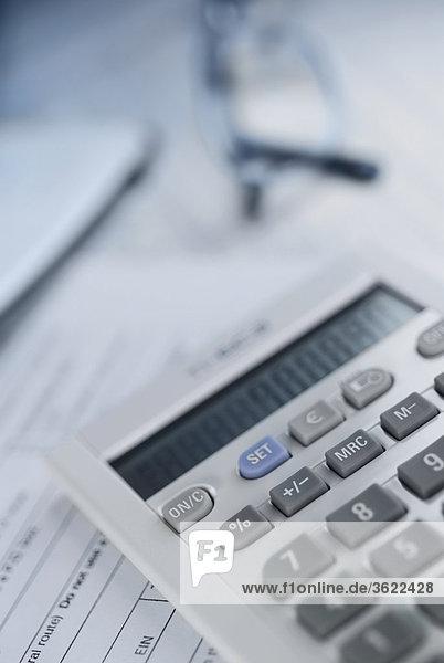 Nahaufnahme Taschenrechner mit einem Paar Brillen auf Dokumente