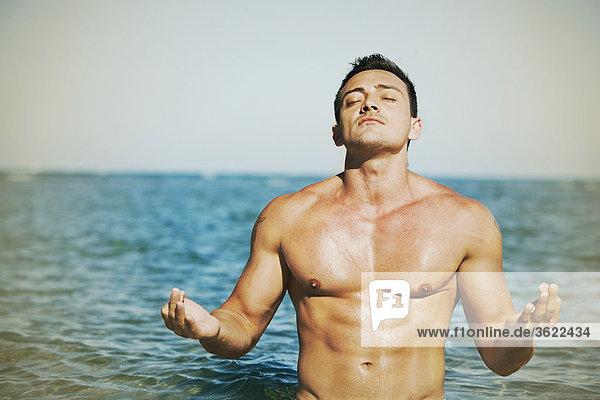 Nahaufnahme eines jungen Mannes Übendes Yoga am Strand