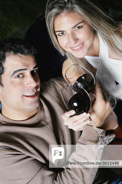 Portrait von Mitte Erwachsenen Mann und eine Mitte erwachsen frau hält Gläser Rotwein und lächelnd