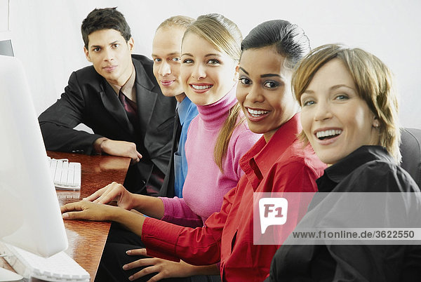 Portrait of business executives sitting in front of a computer