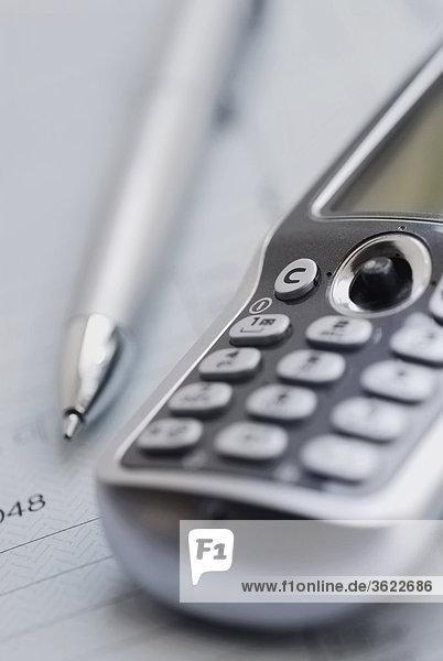 Nahaufnahme eines Stiftes mit einem Mobiltelefon in einem Formular