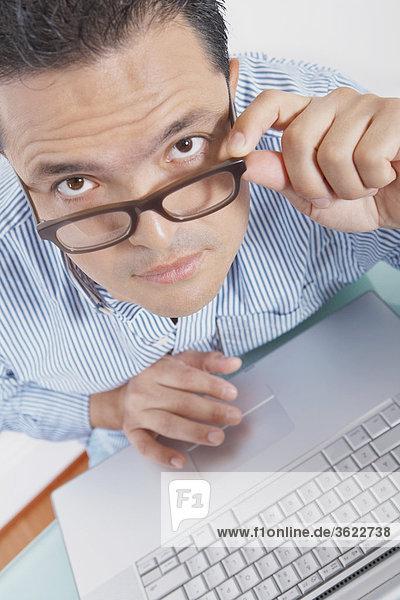 Portrait eines Mitte Erwachsenen Mannes benutze ein Laptop und seine Brillen anpassen
