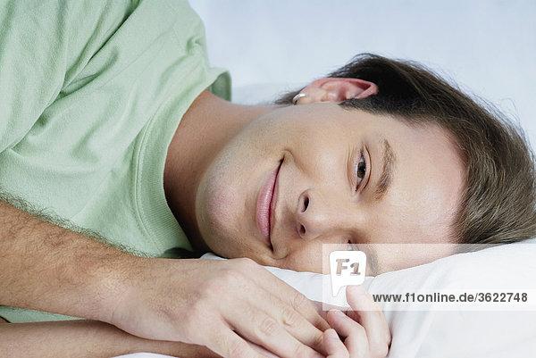 Porträt eines jungen Mannes auf dem Bett liegend und grinsend