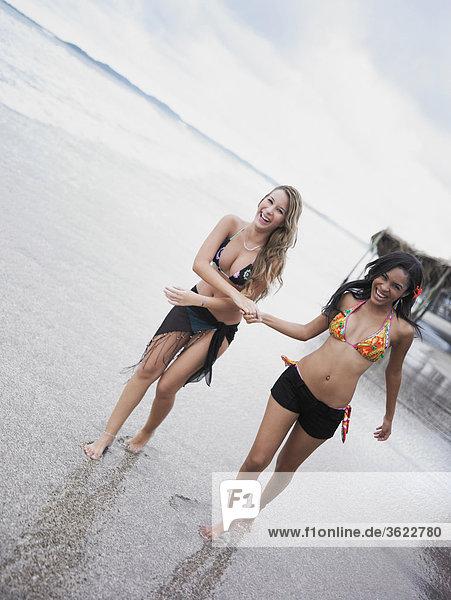Zwei junge Frauen Wandern am Strand und lächelnd