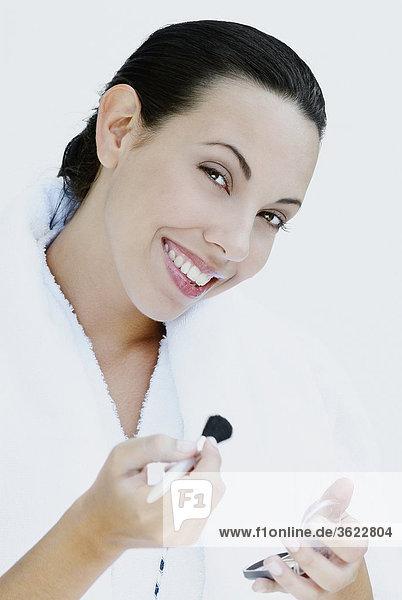 Portrait einer jungen Frau hält einen Make-up Pinsel und lächelnd