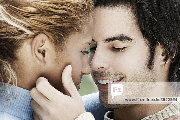 Nahaufnahme eines jungen Mannes eine junge Frau Gesicht berühren