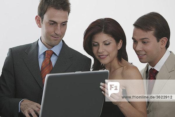 Drei Geschäftsmänner und eine geschäftsfrau  Blick auf einem laptop