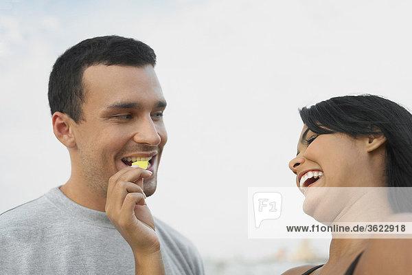 Untersicht einer jungen Frau Fütterung ein Kartoffelchips  einem jungen Mann