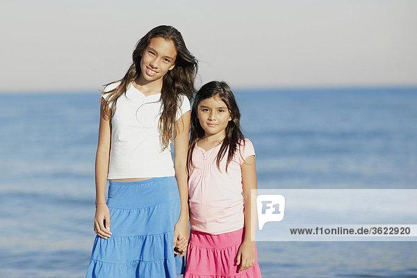 Portrait eines Mädchens und ihre Schwester stehen am Strand