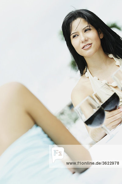 Zwei junge Frauen sitzen am Tisch mit Gläser Wein vor