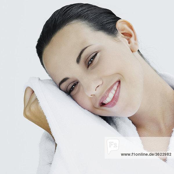 Portrait einer jungen Frau  die ihr Gesicht mit einem Tuch abwischen