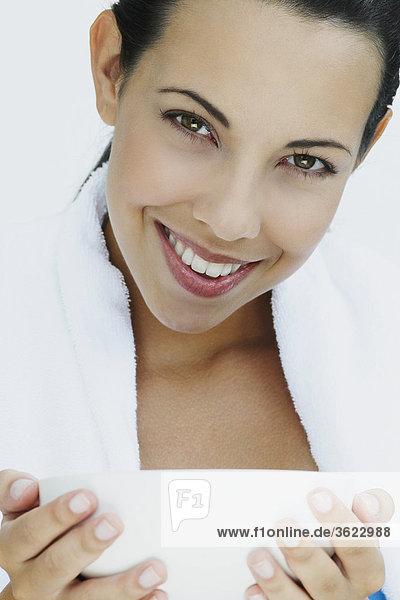 Portrait einer jungen Frau hält eine Schüssel und lächelnd
