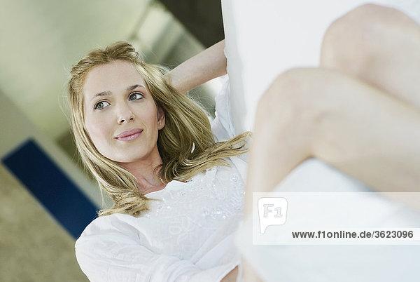 Nahaufnahme einer jungen Frau sitzend mit der Hand im Haar