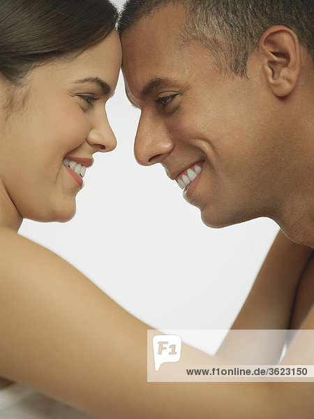 Side profile of a mid adult man looking at a young woman