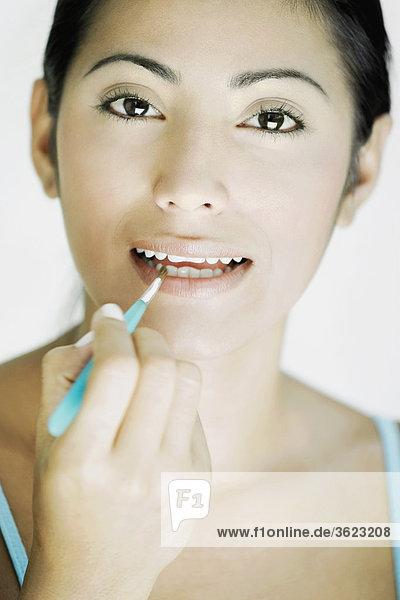 Portrait einer jungen Frau Lippenstift auf ihre Lippen mit einem Make-up Pinsel anwenden