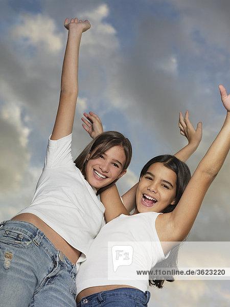 Untersicht ein Teenagerin und ihre Schwester stehen mit ihrem ausgestreckten Armen