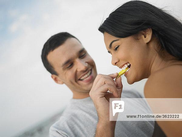 Nahaufnahme eines jungen Mannes Fütterung einer jungen Frau ein Stück Obst