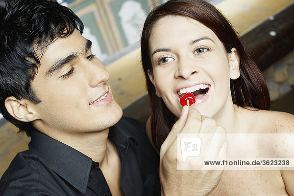 Nahaufnahme eines jungen Mannes Fütterung Kirsche mit einer jungen Frau