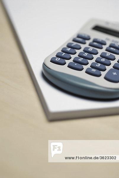 Nahaufnahme des Taschenrechners auf einen Notizblock