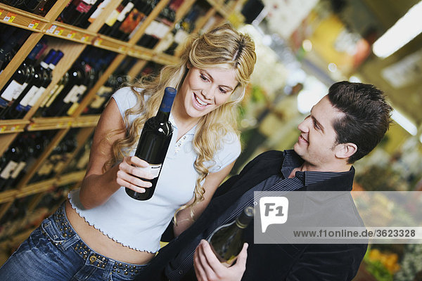 Close-up of a young couple holding wine bottles in a supermarket