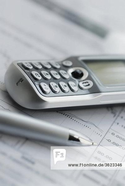 Nahaufnahme von einem Mobiltelefon und einem Stift auf einem Blatt Papier