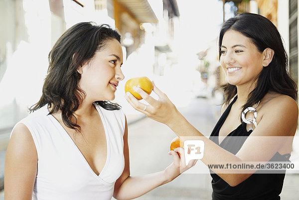 Nahaufnahme der zwei jungen Frauen hält Orangen und Blick auf einander