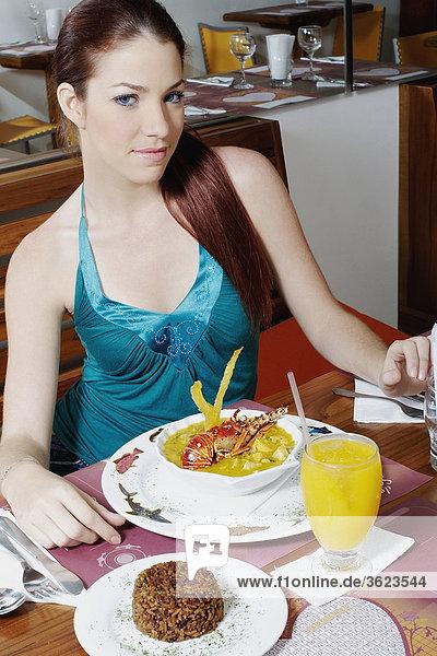 Portrait einer jungen Frau sitzt auf dem Esstisch