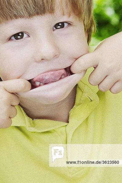 Nahaufnahme eines jungen Mund mit seinen Fingern Dehnung