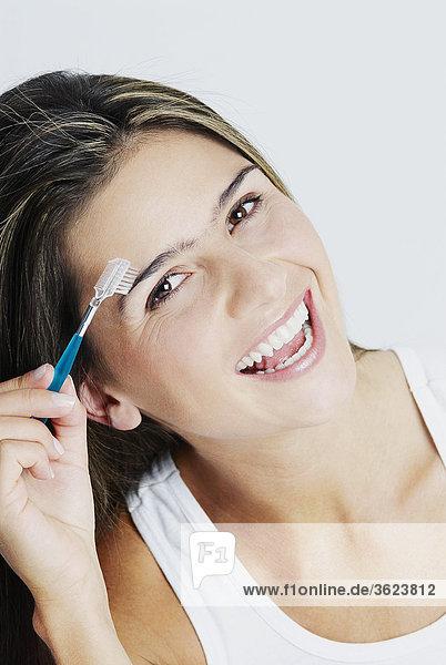 Portrait einer jungen Frau Bürsten ihre Augenbrauen und lächelnd
