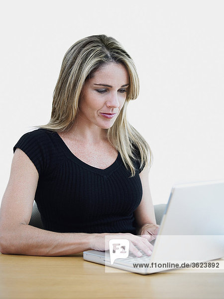 Mid adult woman using a laptop