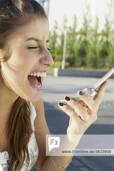 Close-up of a young woman shouting on a mobile phone
