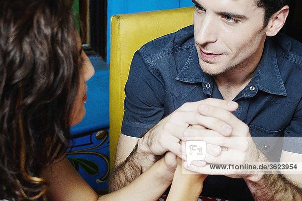 Nahaufnahme eines jungen Paares sitzen und halten einander ist Hände